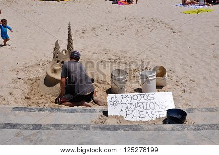 HILLARYS,WA,AUSTRALIA-JANUARY 22,2016: Busker carving a sand sculpture at Hillarys Boat Harbour in Hillarys, Western Australia.