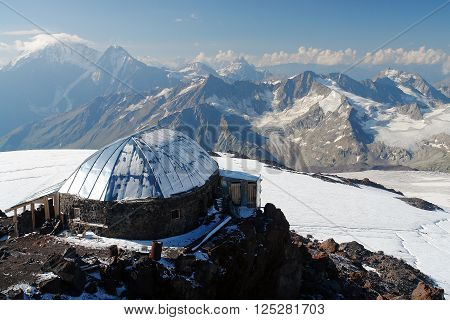 hut stands high in the snowy mountains