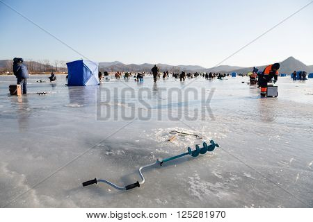 Fisherman ice screws in the foreground, fishing smelt in Russia. Primorsky Krai, Far East.