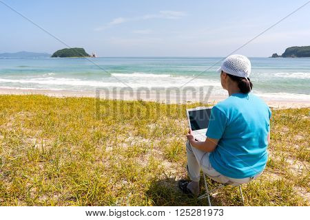 Middle-aged woman uses a personal computer while on the beach on a summer day