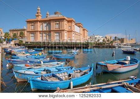 Margherita Theater and fishing row boat in old harbor of Bari