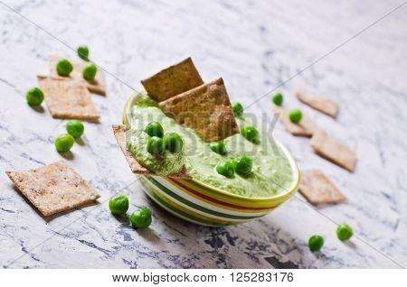 Pea green dip on a cracker. Selective focus.