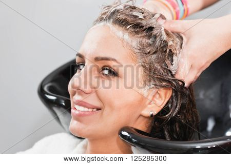 Washing hair in hair salon, looking at camera