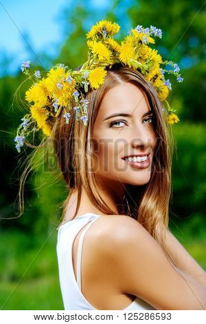 Romantic smiling girl in a wreath of wild flowers. Summer life. Beauty.