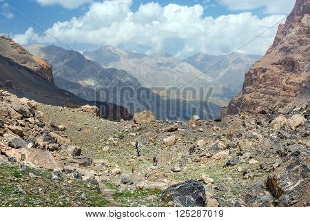 Orange Rocks Several Crests in Remote Perspective. Three People with Backpacks and Trekking Poles Walks on Moraine