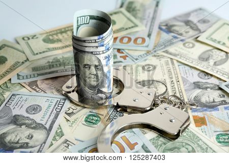 Handcuffs with rolled dollar banknote on paper background. Corruption concept
