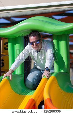 Dark-haired man in sunglasses playing on playground