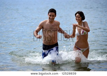 Man an d woman running in the water hand in the hand