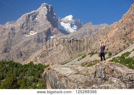Female body on top of Stone Stretching body Towards Sun morning mountain landscape background