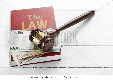 Gavel with book and money on wooden background