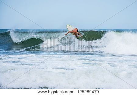 A surfer rides the wave along coast in Spring Lake New Jersey.