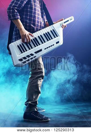 Male hands with synthesizer in smoke
