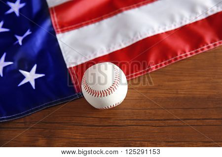 Baseball and American flag on wooden background. Popular sport concept