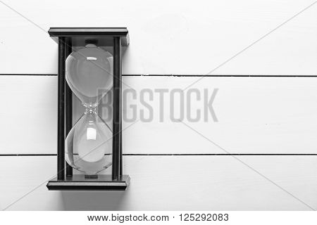 Black sand glass on white wooden background