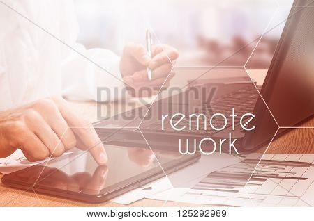 The concept of remote work. Business style dressed man sitting style wooden desk with electronic gadgets around working on laptop sunlight.