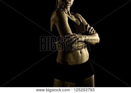 faceless anonymous 40s fit and strong sport woman holding posing defiant in cool attitude with welt built body in gym club harsh light advertising style isolated on black background