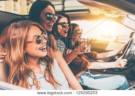 Just keep driving! Side view of four beautiful young cheerful women looking away with smile while sitting in car