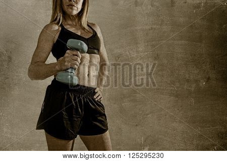 faceless anonymous 40s fit and strong sport woman holding weight on her hand posing defiant in cool attitude with welt built body in gym club harsh light advertising style