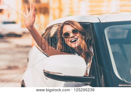 Hello! Beautiful young cheerful women looking at camera with smile and waving while sitting in her car