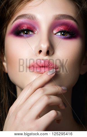 Closeup portrait of young beautiful woman with bright pink smokey eyes and lips. Fashion makeup. Studio shot. Modern summer make up