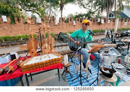 LAMPANG, THAILAND - FEB 19: Lone guitarist playing music on the street fair surrounded by musical instruments on February 19, 2016. Population of Lampang is near 59000 people