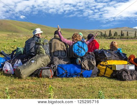 Jolly Company of Tourists Sitting on Large Heap of Travel Luggage Green Meadow of Wild Kirghiz Steppe Expressing Joy and Amazement Blue Sky Hills Background