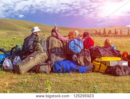Jolly Company Tourists Sitting Heap of Travel Luggage Green Meadow Wild Kirghiz Steppe Expressing Joy and Amazement Shining Sun above Hills on Blue Sky