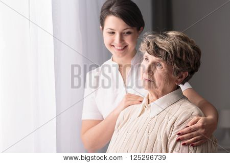 Supportive smiling caregiver visiting her older friend