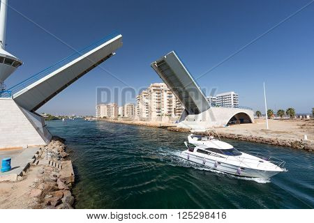 La Manga - SPAIN, AUGUST 25 2014: Drawbridge over water channel and Pleasure boat at summer day