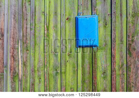 Wooden boards as a background and a mailbox. The texture of the fence. Vintage effect. Boards old peeling green paint and blue mailbox for letters. Copy space.