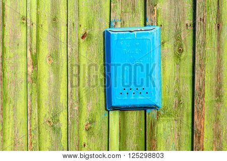 Wooden boards as a background and a mailbox. The texture of the fence. Vintage effect. Boards old peeling green paint and a mailbox for letters. Copy space.