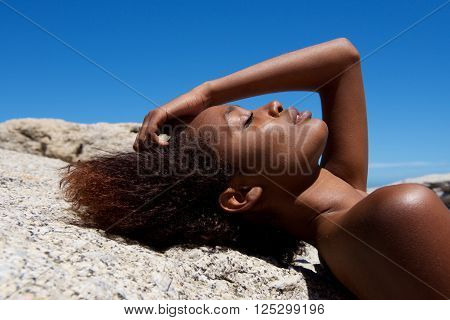 Attractive Female Model Lying On Rock Outdoors