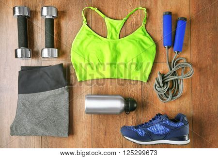 Athlete's set with female clothing, bottle of water and equipment on wooden background
