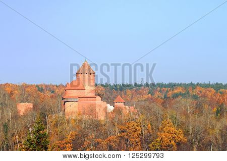 Medieval castle of Livonia order in Sigulda, Latvia. Red brick tower in a forest.