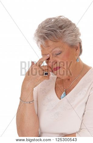 A closeup image of a very sad looking senior citizen woman in her seventies with short grey hair isolated for white background.