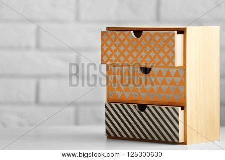 Handmade chest of drawers for jewelry on wooden table against wall background