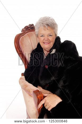 A lovely senior woman in a black fur coat laughing sitting in a pink armchair isolated for white background.