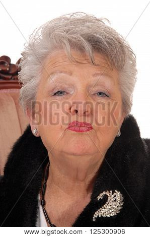 Lovely elderly woman giving a kiss in a closeup portrait image with gray white hair isolated for white background.
