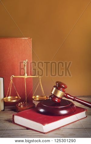 Wooden gavel with justice scales and books on brown background