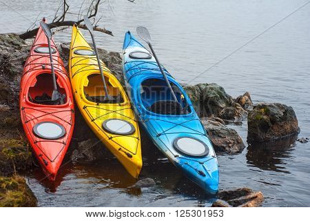 Colorful Fiberglass Kayaks Lying On The Rocky Shore01