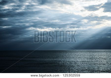 Dramatic sunbeams in the sea before storm. Beautiful cloudscape with sun rays.