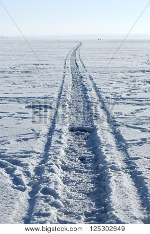 Road on a frozen lake. Car tracks on snow covering ice.