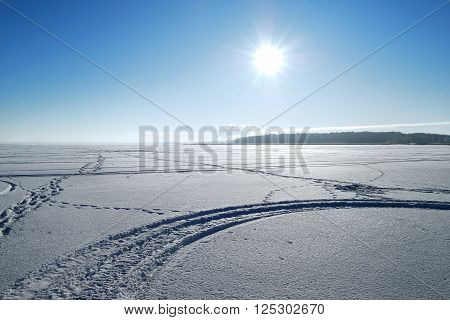 Sun above frozen winter landscape. Arctic desert with tracks and footprints in snow.