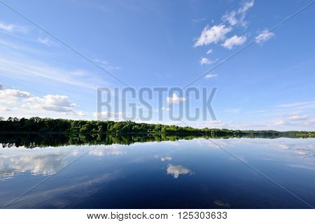 River landscape. Green forest and blue sky reflecting in still water.
