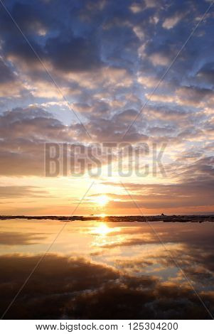 Sunset at the sea shore. Beautiful sky reflecting in still water.