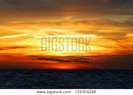 Colorful sunset in the sea. Golden and orange featherlike clouds.