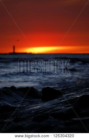 Dramatic red sunset at the sea shore. Stormy dark sea waves.