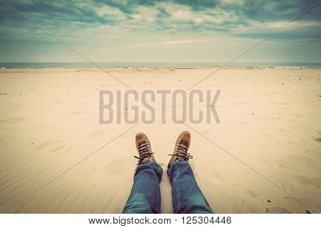 First person perspective of man legs in jeans on the autumn beach. Vintage, retro style