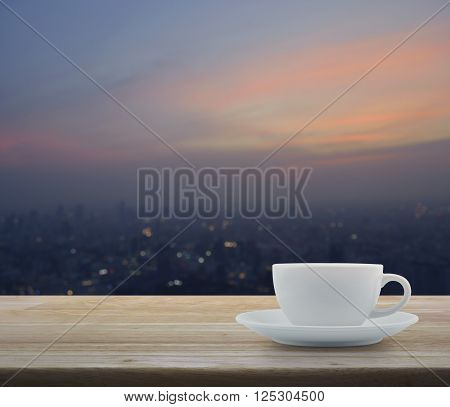White cup on wooden table with blurred aerial view of cityscape on warm light sundown
