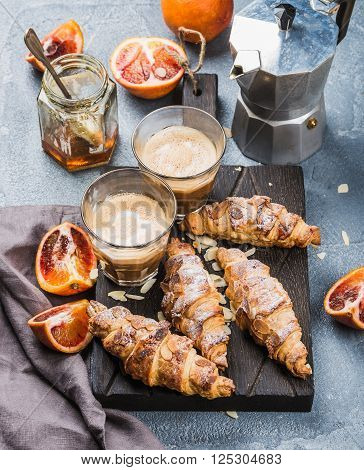Italian style home breakfast. Latte coffee, almond croissants and red bloody oranges on dark wooden serving  board over concrete textured table, moka pot and honey jar at background, selective focus